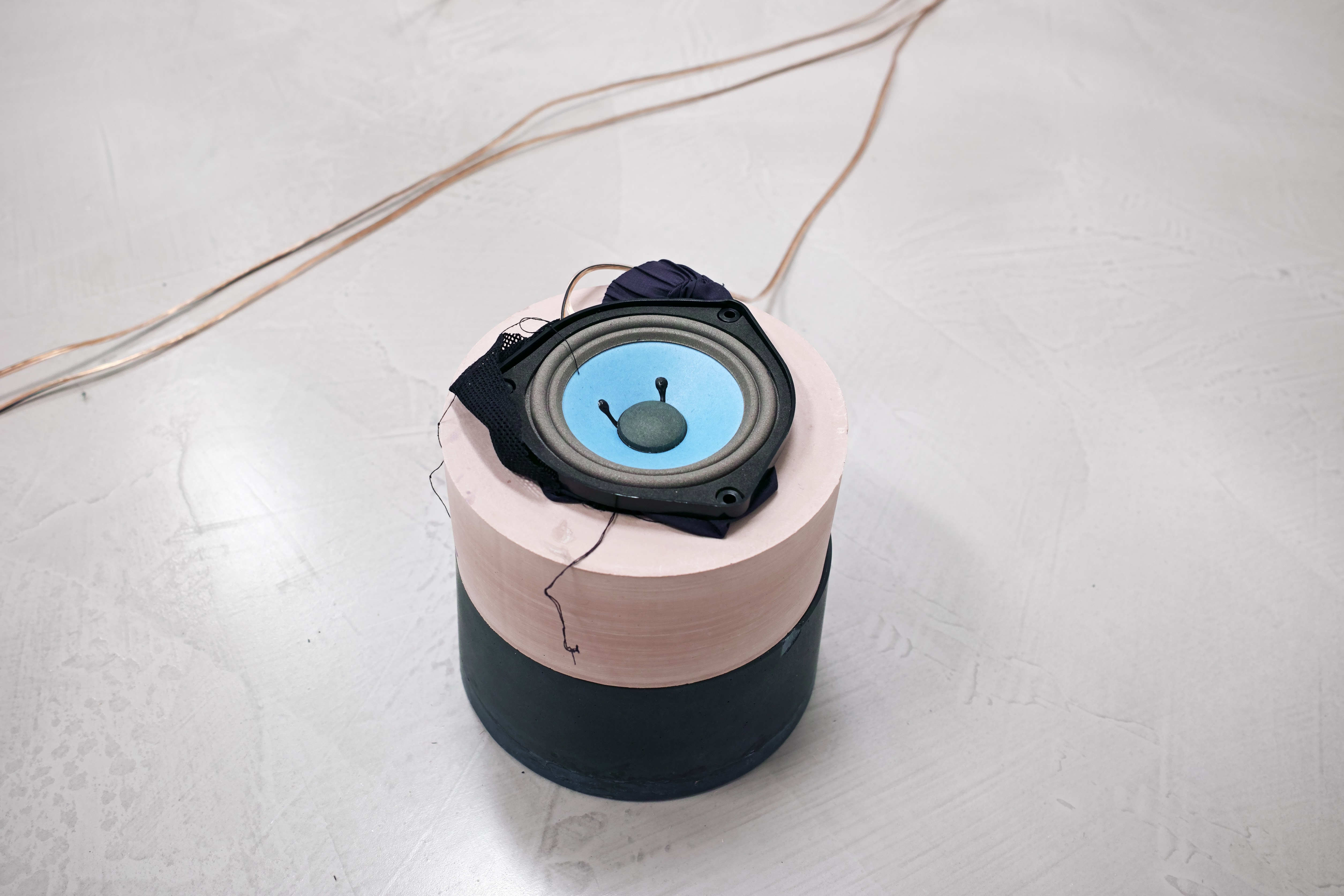 Speaker, pigmented Jesmonite, Polyester and fleece fabric, urban debris, copper audio cable
